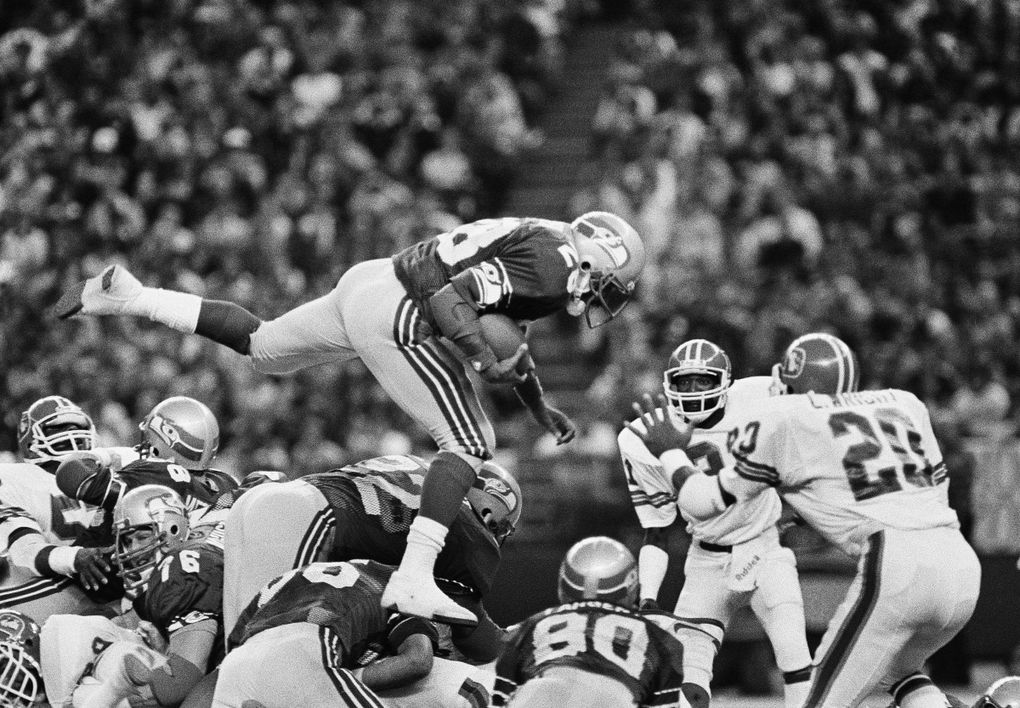 Seattle Seahawk running back Curt Warner leaps over a pile of players as he gains yardage against the Denver Broncos in the Kingdome at Seattle, on Dec. 25, 1983. Warner gained 99 yards on 23 carries as the Seahawks beat the Broncos in their NFL wildcard game 31-7.  (Jeff Larson / AP)