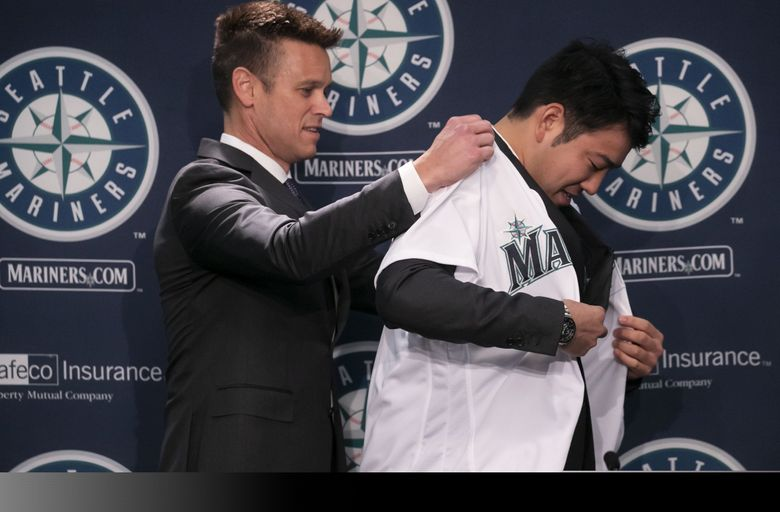 Mariners general manager Jerry Dipoto puts a jersey on new pitcher Yusei Kikuchi last Thursday. (Erika Schultz / The Seattle Times)