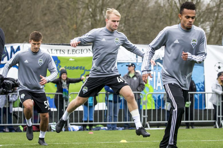 Top draft pick Tucker Bone does a leaping warmup stretch on the first day of Sounders training camp at their practice facility in Tukwila this week. (Bettina Hansen / The Seattle Times)