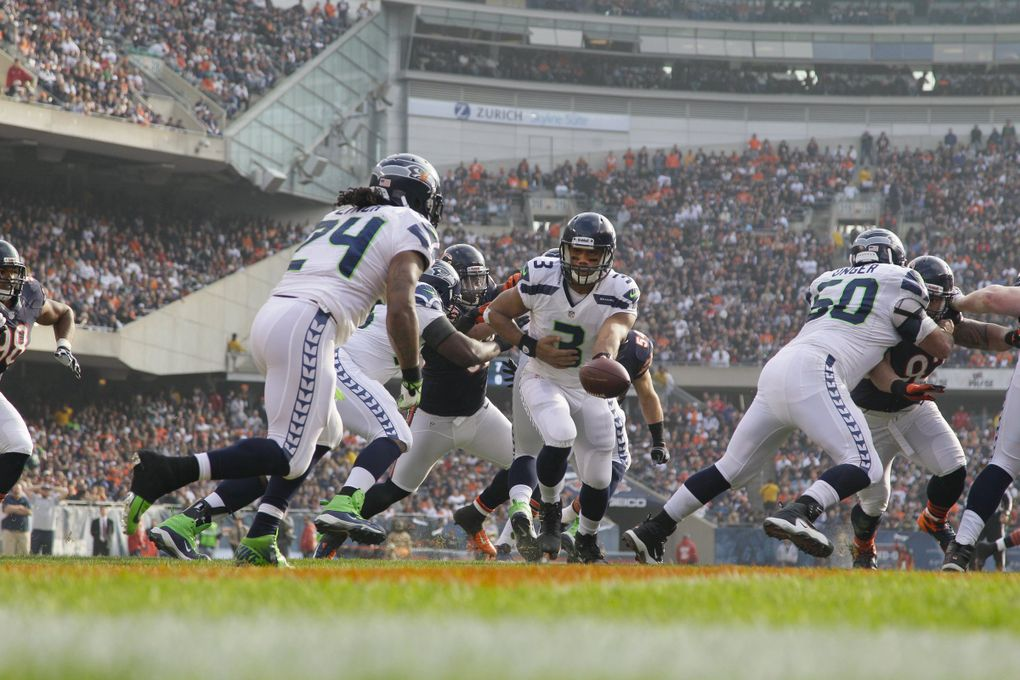 Seattle Seahawks quarterback Russell Wilson (3) hands off to running back Marshawn Lynch (24) in the first half of an NFL football game in Chicago, Sunday, Dec. 2, 2012.  (Nam Y. Huh / The Associated Press)