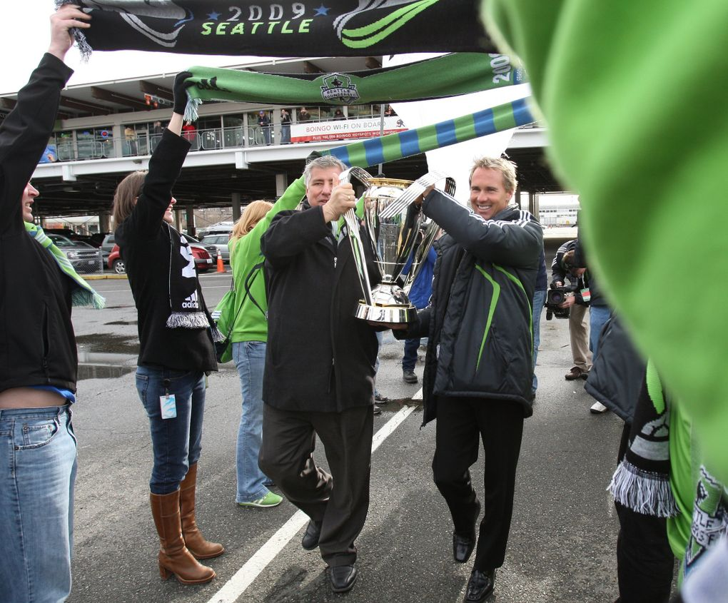 Former MLS Cup winners, Sounders head coach, Sigi Schmid and Chris Henderson walk off a ferry at the Seattle Ferry terminal carrying the MLS Cup–arriving in dramatic fashion to stir up support for this Sunday's MLS championship game between Real Salt Lake and the L.A. Galaxy. They are walking under scarfs held by Sounders fans.   (Steve Ringman / The Seattle Times)