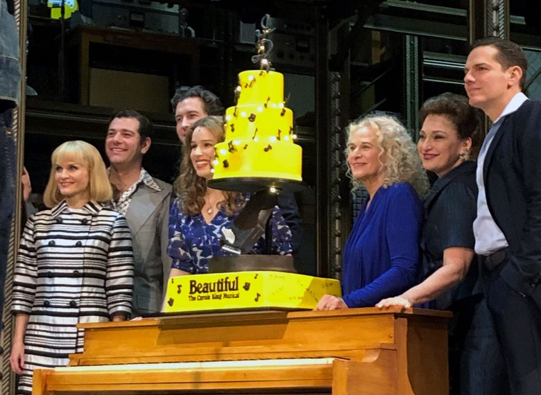 """In this Saturday, Jan. 12, 2019, photo Carole King, third from right, poses for photos with the cast of """"Beautiful: The Carole King Musical"""" at the Stephen Sondheim Theatre after a performance in New York. King appeared Saturday night, sitting at a baby grand piano and showing all the love in her heart as she sang """"Beautiful,"""" the final song to celebrate the show's fifth anniversary on Broadway. (AP Photo/Brooke Lefferts)"""