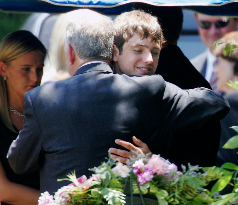 FILE – In this June 29, 2006, file photo, John Ramsey hugs his son, Burke, facing camera, at the graves of his wife, Patsy, and daughter JonBenet, during services for his wife at the St. James Episcopal Cemetery in Marietta, Ga. A $750 million defamation lawsuit filed against CBS by Burke Ramseu, the brother of JonBenet Ramsey, has been settled on Wednesday, Jan. 2, 2019. The Daily Camera reports court records show that a Michigan Circuit Court judge,  dismissed the lawsuit filed by Burke Ramsey in December 2016. (AP Photo/Ric Feld, File)