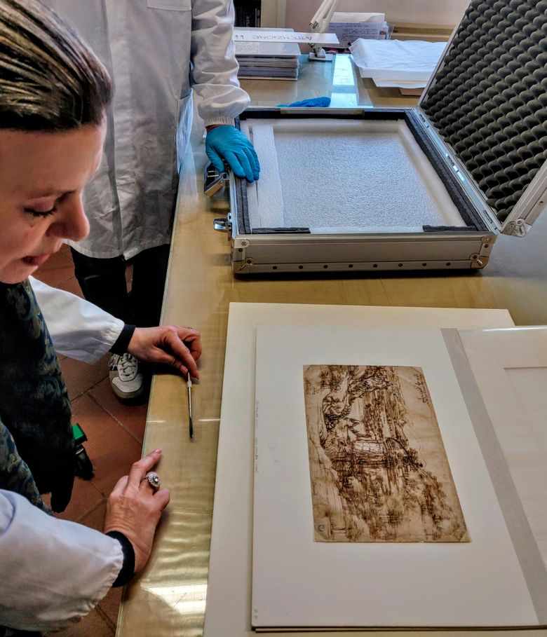 """In this photo provided by the Opera Laboratori on Thursday, Jan. 17, 2019, a drawing by Leonardo Da Vinci is observed after being removed from a briefcase which carried it from the Uffizi Gallery to the Opificio delle Pietre Dure where it will undergo scientific analysis, in Florence, Italy. First-ever scientific study of a Leonardo drawing done in his youth shows the artist added details to earlier sketch. The Uffizi Galleries said that 1473 """"Landscape Drawing for Santa Maria della Neve"""" was taken on Thursday to a Florence restoration for scientific analyses. (Opera Laboratori via AP)"""