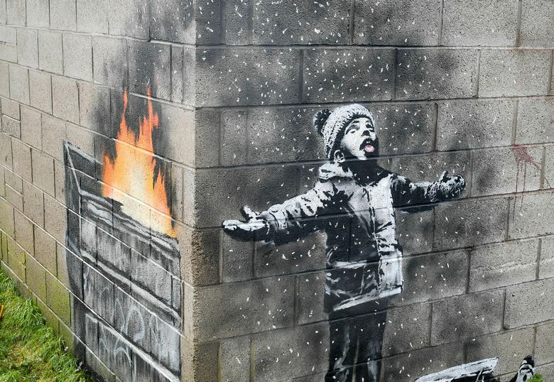 """FILE –  In this file photo dated Dec, 20, 2018, showing an artwork by Banksy on the side of a garage depicts a child dressed for snow playing in the falling ash and smoke from a skip fire, in Port Talbot, Wales.  The artwork has been sold to an Essex art dealer for a """"six-figure sum"""", although the mural will stay in its current location for about two-years, it is revealed Friday Jan. 18, 2019. (Ben Birchall/PA FILE via AP)"""