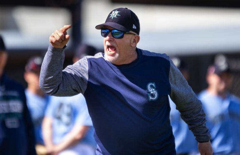 Mariners coach Perry Hill runs the team through infield drills Saturday at Peoria Sports Complex. (Dean Rutz / The Seattle Times)
