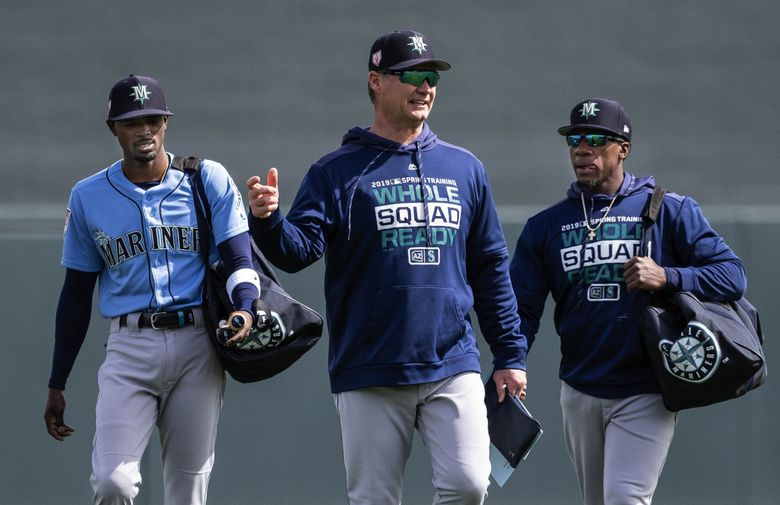 Mariners skipper Scott Servais arrives at a spring training game flanked by Dee Gordon, left, and Shed Long. (Dean Rutz / The Seattle Times)