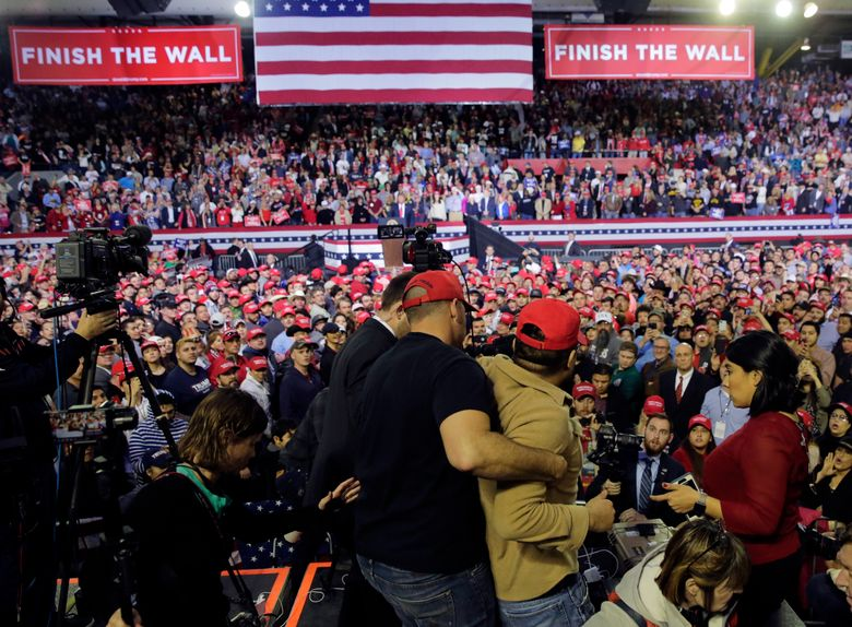 A man is restrained after he began shoving members of the media during a rally for President Donald Trump at the El Paso County Coliseum, Monday, Feb. 11, 2019, in El Paso, Texas. (AP Photo/Eric Gay)