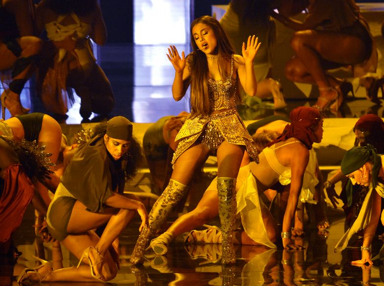 """FILE – In this Aug. 20, 2018, file photo, Ariana Grande, center, performs """"God is a woman"""" at the MTV Video Music Awards at Radio City Music Hall in New York. A Las Vegas artist is suing pop music star Grande, alleging federal copyright infringement over an image of a woman in a candle flame in the pop star's widely-viewed """"God is a Woman"""" music video. Representatives for Grande did not immediately respond Monday, Feb. 4, 2019, to messages about the lawsuit filed Thursday in U.S. District Court in Nevada by attorneys for Vladimir Kush and his company Kush Fine Arts Las Vegas. (Photo by Chris Pizzello/Invision/AP, File)"""