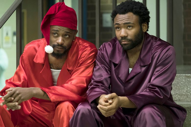 """This image released by FX shows Lakeith Stanfield, left, and Donald Glover in a scene from the comedy series """"Atlanta."""" Glover's comedy """"Atlanta"""" will be back. Just not as soon as expected. FX Networks CEO John Landgraf told a TV critics' meeting on Monday, Feb. 4, that the series is behind schedule. (Guy D'Alema/FX via AP)"""
