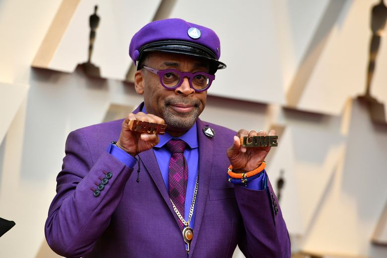 """Spike Lee holds up brass knuckles reading """"hate"""" and """"love"""" from his iconic film """"Do The Right Thing"""" as he arrives at the Oscars on Sunday, Feb. 24, 2019, at the Dolby Theatre in Los Angeles. (Photo by Jordan Strauss/Invision/AP)"""