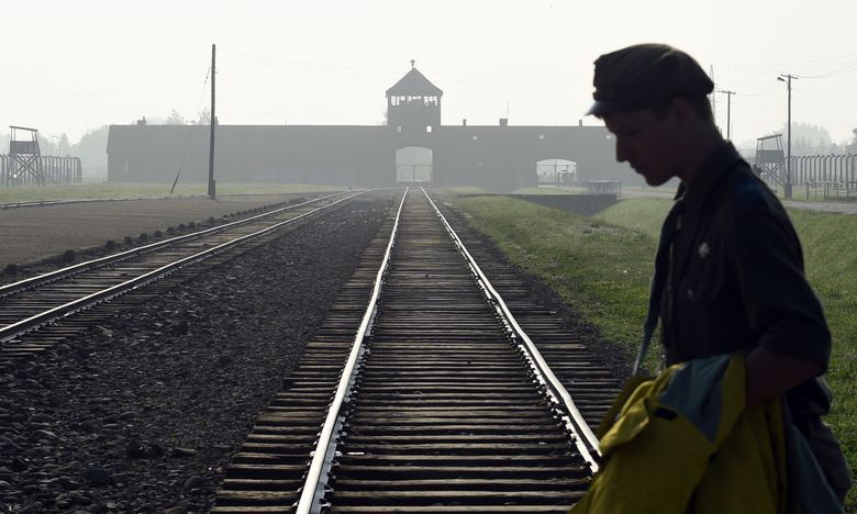FILE – In this file photo dated Friday, July 29, 2016, a man crosses the iconic rails leading to the former Nazi death camp of Auschwitz-Birkenau in Poland.  Police official Malgorzata Jurecka in Poland said Sunday March 31, 2019, an American visitor to the former Auschwitz-Birkenau death camp attempted to steal a metal part of the rail tracks where prisoners were unloaded, and he has been charged with attempted theft. (AP Photo/Alik Keplicz, FILE)
