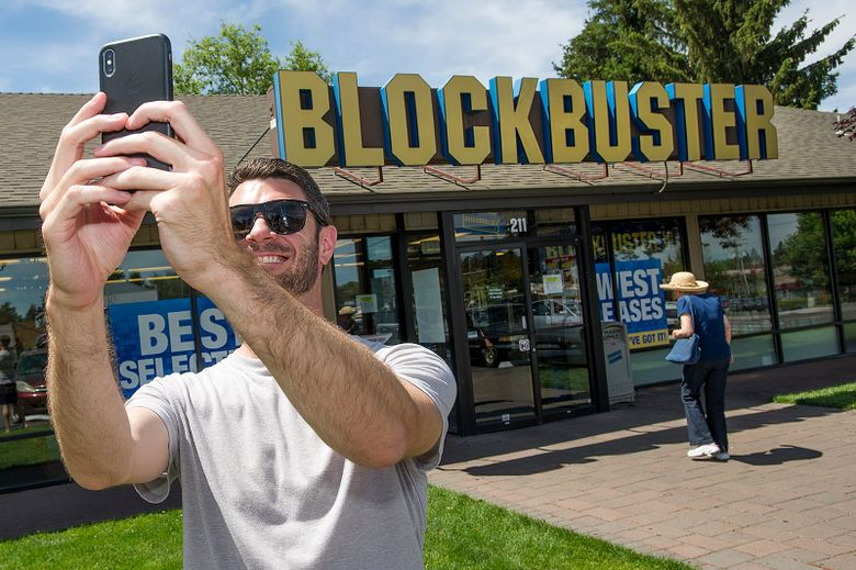 Scott Thornton takes a selfie last year in front of the Bend, Ore., Blockbuster. The store became the last one in the U.S. last year, and now it's the only one in the world. (Ryan Brennecke / The Bulletin via AP, file)