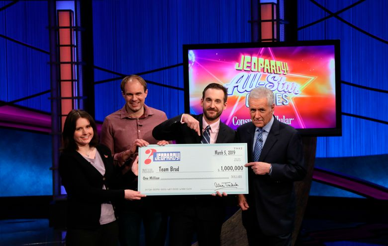 """From left, Larissa Kelly, Brad Rutter and David Madden with Alex Trebek at the end of the """"Jeopardy!"""" team championship on Tuesday in Burbank, Calif. (Carol Kaelson / Sony via AP)"""