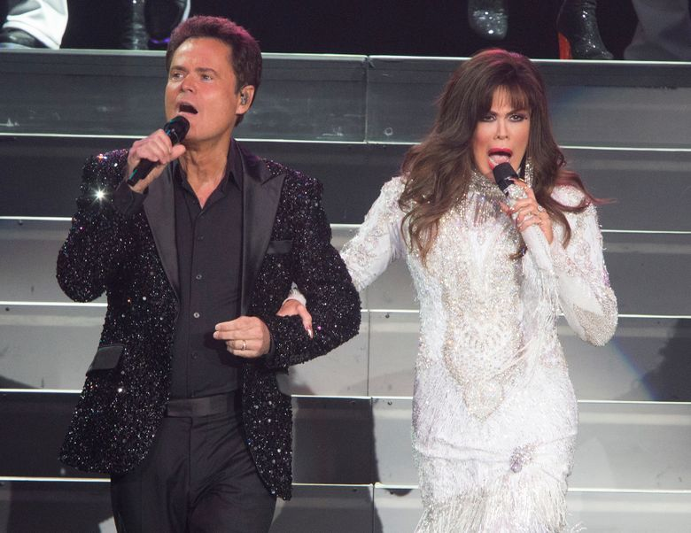 """FILE – This Aug. 22, 2017 file photo shows Donny Osmond, left, and Marie Osmond performing at the Santander Arena in Reading, Pa. Donny and Marie Osmond say they will end their Las Vegas show later this year, concluding an 11-year run on the Strip. The brother-sister duo made the announcement during an appearance on """"Good Morning America"""" on Thursday, March 21, 2019. Their final performance at the Flamingo Las Vegas is scheduled for Nov. 16. (Photo by Owen Sweeney/Invision/AP, File)"""