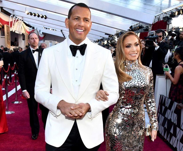 FILE – In this Sunday, Feb. 24, 2019, file photo, Alex Rodriguez, left, and Jennifer Lopez arrive at the Oscars at the Dolby Theatre in Los Angeles. Rodriguez and Lopez are engaged. The couple posted an Instagram photo of their hands with a massive engagement ring on Lopez's ring finger. (Photo by Charles Sykes/Invision/AP, File)