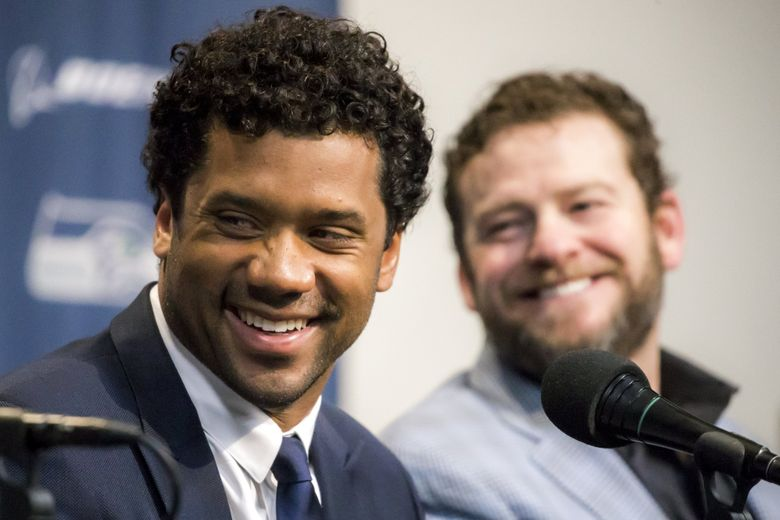Seahawks quarterback Russell Wilson and general manager John Schneider speak at a news conference Wednesday. Earlier this week, Wilson and the Seahawks agreed to a four-year, $140 million contract extension and $65 million signing bonus. The deal keeps him with the Seahawks through the 2023 season and makes him the highest-paid player in the history of the NFL. (Bettina Hansen / The Seattle Times)