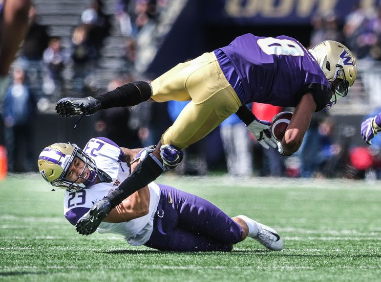 Defensive back Brandon McKinney upends wide receiver Marquis Spiker.  Washington held its 2019 Husky Spring Football Preview at Husky Stadium Saturday, April 27, 2019. (Dean Rutz / The Seattle Times)
