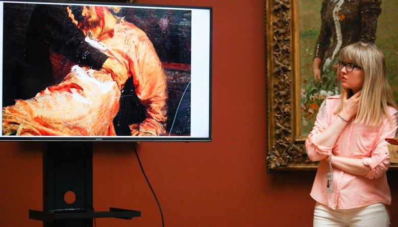 FILE – In this file photo taken Tuesday, May 29, 2018, A museum employee looks at the screen depicting the damage inflicted to a painting by Russian painter Ilya Repin in an attack at the Tretyakov State Gallery in Moscow, Russia.  A court in Moscow on Tuesday April 30, 2019, sentenced a man to two and a half years in prison for vandalizing the famous painting by renowned Russian artist Ilya Repin. (Sergey Vedyashkin, Moscow News Agency photo via AP, File)