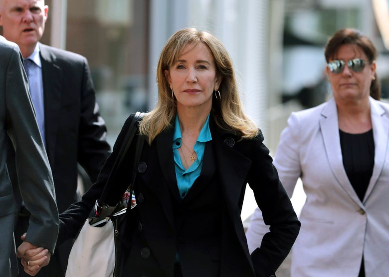 FILE – This April 3, 2019 file photo shows actress Felicity Huffman arriving at federal court in Boston to face charges in a nationwide college admissions bribery scandal. Huffman is facing a prison sentence after agreeing Monday to plead guilty to one count of conspiracy and fraud for paying a consultant $15,000 disguised as a charitable donation to boost her daughter's SAT score. Prosecutors are seeking four to 10 months of confinement, and experts different on whether the plea, and Huffman's subsequent apology taking full responsibility for her actions, will lead to a career rebound or retreat. (AP Photo/Charles Krupa, File)