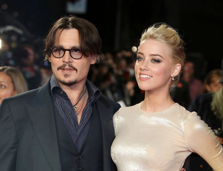 """FILE – In this Nov. 3, 2011 file photo, U.S. actors Johnny Depp, left, and Amber Heard arrive for the European premiere of their film, """"The Rum Diary,"""" in London.Heard is asking a judge to dismiss a $50 million defamation lawsuit her ex-husband Johnny Depp filed over a Washington Post op-ed she wrote about domestic violence. In the motion filed Thursday in Fairfax, Virginia, Heard's lawyers reiterate allegations that Depp abused her and include exhibits such as photos of her with bruised face and scarred arms. (AP Photo/Joel Ryan, File)"""