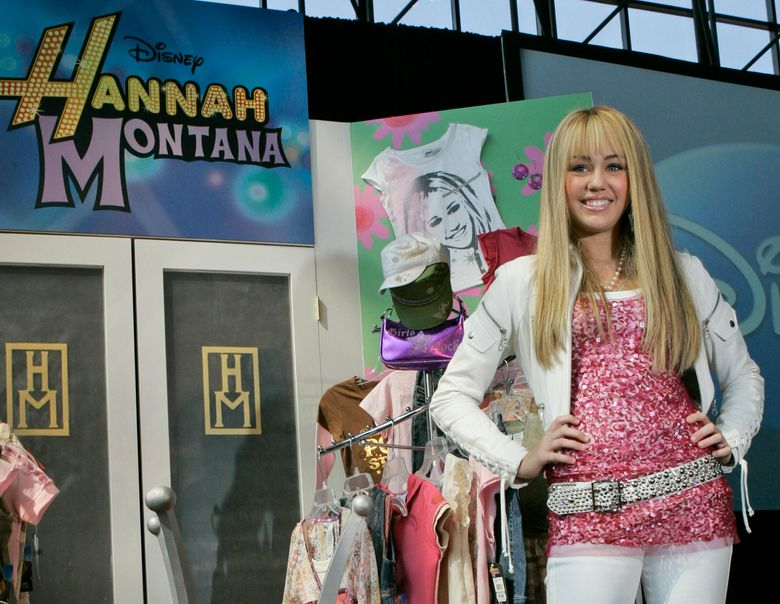 """FILE – In this June 19, 2007 file photo Miley Cyrus, star of The Disney Channel's series """"Hannah Montana"""" makes an appearance at the Licensing International Expo in New York. Costumes, props and tour items from the Disney Channel's """"Hannah Montana"""" TV series are going up for auction. The teen sitcom featured Cyrus, who portrayed schoolgirl Miley Stewart by day and international pop star Hannah Montana by night. It helped launched Cyrus' career and the franchise included albums, films and concerts. Julien's Auctions announced on Thursday, April 11, 2019, all proceeds will benefit the Wilder Minds charity, which aids the world's at-risk animals.  (AP Photo/Mary Altaffer, File)"""