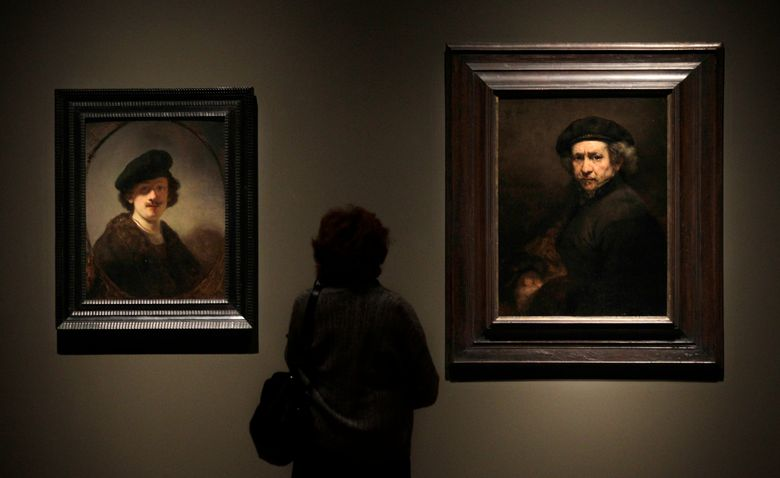 FILE – In this file photo dated Thursday, Feb. 16, 2012, a visitor views two self portraits by 17th century Dutch master Rembrandt at the Cleveland Museum of Art's 'Rembrandt in America' exhibition in Cleveland, USA.  It is announced Monday April 8, 2019, Dutch soccer teams will be playing with the official soccer ball inscribed with Rembrandt's face and extracts from his work in the Dutch soccer league next season, marking the 350th anniversary of his death.(AP Photo/Amy Sancetta, FILE)