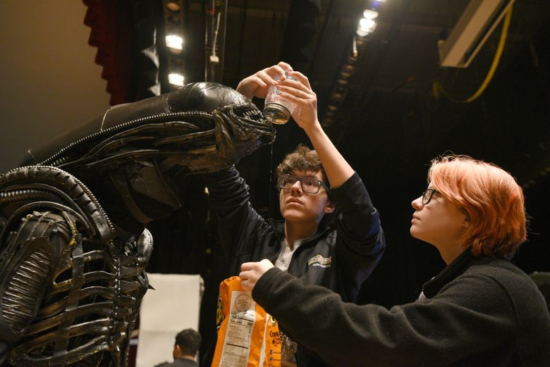 """FILE – In this March 25, 2019 file photo, North Bergen High School's Xavier Perez, 16, the Alien, is covered in slime by his handlers Eddie Mantilla, 15, and Cassandra Klima, 16, as they work on the play """"Alien,"""" an adaptation of the Ridley Scott movie, in North Bergen, N.J. The New Jersey high school's stage production of """"Alien"""" is coming back with help from the 1979 film's director, Ridley Scott, after his production company provided $5,000 so the school could put on an encore performance April 26. On Friday, April 26, 2019, Sigourney Weaver was at the school to watch the encore performance herself, telling the crowd before the curtain rose that """"this is the night I've been waiting for."""" (Amy Newman/The Record via AP)"""