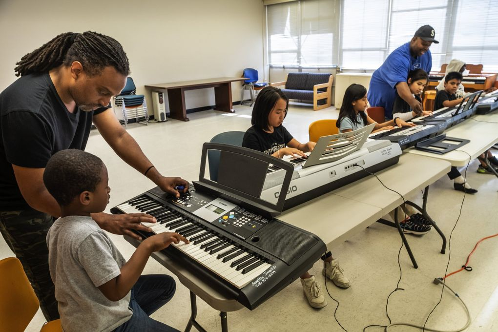 Darrius Willrich teaches keyboards to Khalil Jeffries at JazzED. Sherrell Mitchell, standing, is another teacher/musician with the program. (Dean Rutz / The Seattle Times)