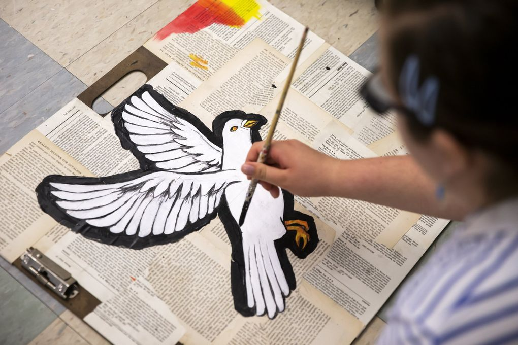 """Alexandra Lawson-Mangun, 16, a Franklin High School sophomore, paints a white dove as part of the set for the play """"Don't Call it a Riot!"""" (Bettina Hansen / The Seattle Times)"""