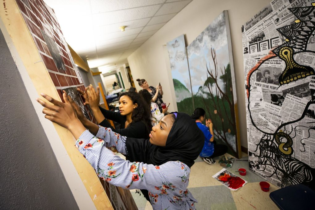 """Franklin High School seniors Isatou Ceesay, 17, foreground, and Asia Hemphill, 18, paste a poster on a """"brick wall"""" for the upcoming play """"Don't Call it a Riot!,"""" which explores activism in Seattle from the Black Panther Party of the 1960s to the WTO protests in 1999. (Bettina Hansen / The Seattle Times)"""
