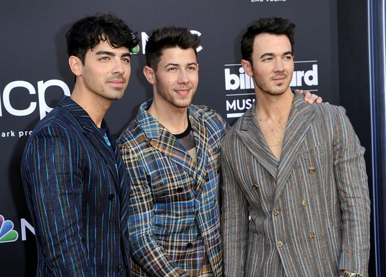 """FILE – This May 1, 2019 file photo shows Joe Jonas, from left, Nick Jonas and Kevin Jonas, of the Jonas Brothers, at the Billboard Music Awards in Las Vegas. The brothers have signed a deal with Macmillan to publish their memoir. The book will delve into the band's formation, rise to stardom, breakup in 2013 and reconciliation as a music group earlier this year. """"Blood"""" will hit stores Nov. 12. (Photo by Richard Shotwell/Invision/AP, File)"""