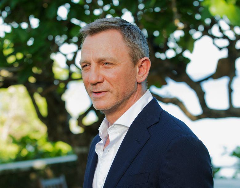 """FILE – In this April 25, 2019, file photo, actor Daniel Craig poses for photographers during the photo call of the latest installment of the James Bond film franchise, currently known as """"Bond 25,"""" in Oracabessa, Jamaica. James Bond is out of commission for a few weeks. Craig is undergoing minor ankle surgery after sustaining an injury while filming the 25th installment in the franchise in Jamaica, according to a tweet from the official James Bond twitter account Wednesday, May 22. (AP Photo/Leo Hudson, File)"""