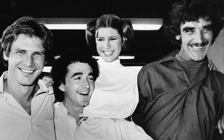 """ADDS NAME OF CARRIE FISHER'S CHARACTER AND BYLINE – FILE – In this Oct. 5, 1978, file photo, actors featured in the """"Star Wars"""" movie, from left, Harrison Ford who played Han Solo, Anthony Daniels who played the robot C3P0, Carrie Fisher who played Princess Leia, and Peter Mayhew who played the Wookie, Chewbacca, are shown during a break from the filming of a television special presentation in Los Angeles. Mayhew, who played the rugged, beloved and furry Wookiee Chewbacca in the """"Star Wars"""" films, has died. Mayhew died at his home in north Texas on Tuesday, April 30, 2019, according to a family statement. He was 74. (AP Photo/George Brich, File)"""