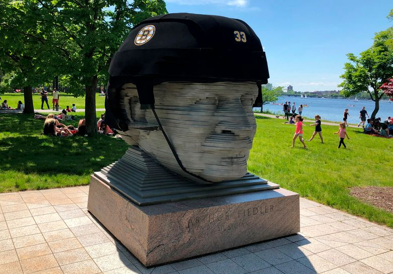 In this May 27, 2019, photo provided by Michael Nichols, a giant Boston Bruins helmet rests atop a statue of the late conductor Arthur Fiedler on the Charles River Esplanade park Monday, May 27, 2019, to cheer on the team in Game 1 of the NHL hockey Stanley Cup finals. The nonprofit Esplanade Association installed the helmet, which has a circumference of 17 feet (5 meters). (Michael Nichols via AP)