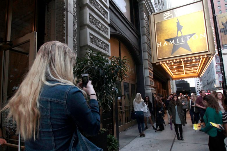 """FILE – In this Oct. 4, 2017 file photo, Alex Richards takes a photo of Meera Ganesh outside the CIBC Theatre after watching """"Hamilton: An American Musical"""" in Chicago. The musical """"Hamilton"""" will end its more than three-year run in Chicago in January. Producers made the announcement Thursday, saying the production playing at downtown Chicago's CIBC Theatre would close Jan. 5, 2020. (AP Photo/Carrie Antlfinger, File)"""