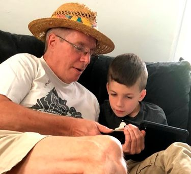 """This summer 2018 photo provided by Al Mattin on Friday, May 10, 2019 shows his father, Stephen, and son, Ronan, at Stephen's home in Kensington, N.H. The Handel & Haydn Society had just finished a rendition of Mozart's """"Masonic Funeral"""" at Boston's Symphony Hall on Sunday, May 5, 2019 when a youngster blurted out: """"WOW!"""" The group was so charmed that they launched a search. Stephen Mattin, who attended the concert with Ronan said he is on the autism spectrum and expresses himself differently from how other people do. He said his grandson is a huge music fan. (Al Mattin via AP)"""