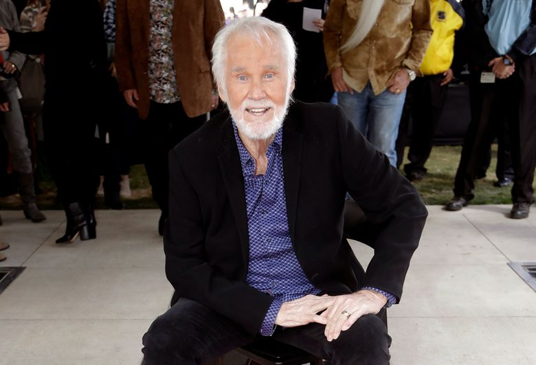 """FILE – In this Oct. 24, 2017 file photo, Kenny Rogers poses with his star on the Music City Walk of Fame in Nashville, Tenn. Rogers has been admitted to a Georgia hospital for dehydration, according to his official Twitter account. A statement posted Friday, May 31, 2019,  said he would remain there for physical therapy to """"get his strength back"""" before being discharged. (AP Photo/Mark Humphrey, File)"""