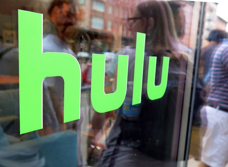 FILE – This June 27, 2015, file photo, shows the Hulu logo on a window at the Milk Studios space in New York. Disney has struck a deal with Comcast that gives it full control of streaming service Hulu. The companies said Tuesday, May 14, 2019, that as early as January 2024 Comcast can require Disney to buy NBCUniversal's 33% interest in Hulu and Disney can require NBCUniversal to sell that stake to Disney for its fair market value at that future time. (AP Photo/Dan Goodman, File)