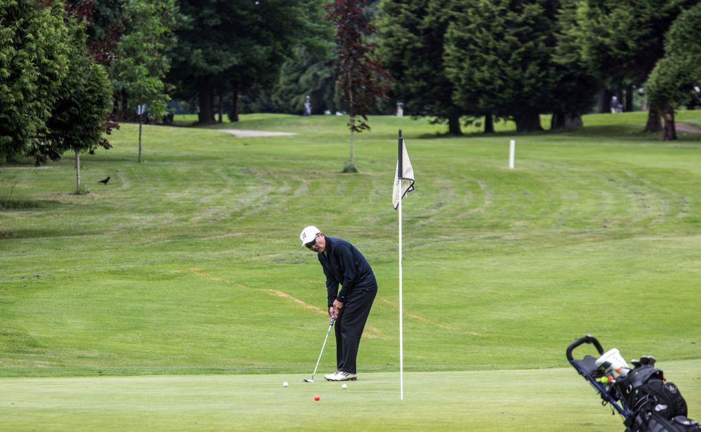 A golfer putts on the second green at Jefferson Golf Course in Seattle on Wednesday.  (Steve Ringman / The Seattle Times)
