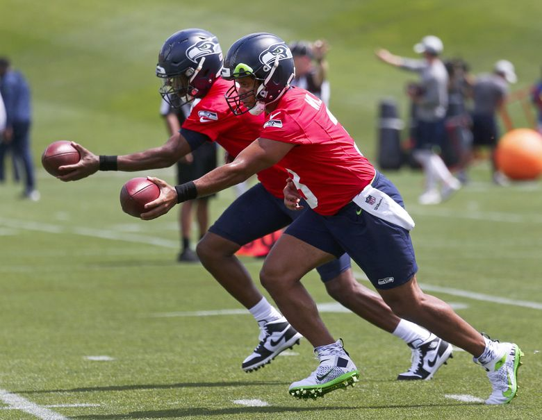 Quarterbacks Russell Wilson (foreground) and Geno Smith (background) at Seahawks minicamp, Wednesday, June 12, 2019 at VMAC in Renton. (Ken Lambert / The Seattle Times)