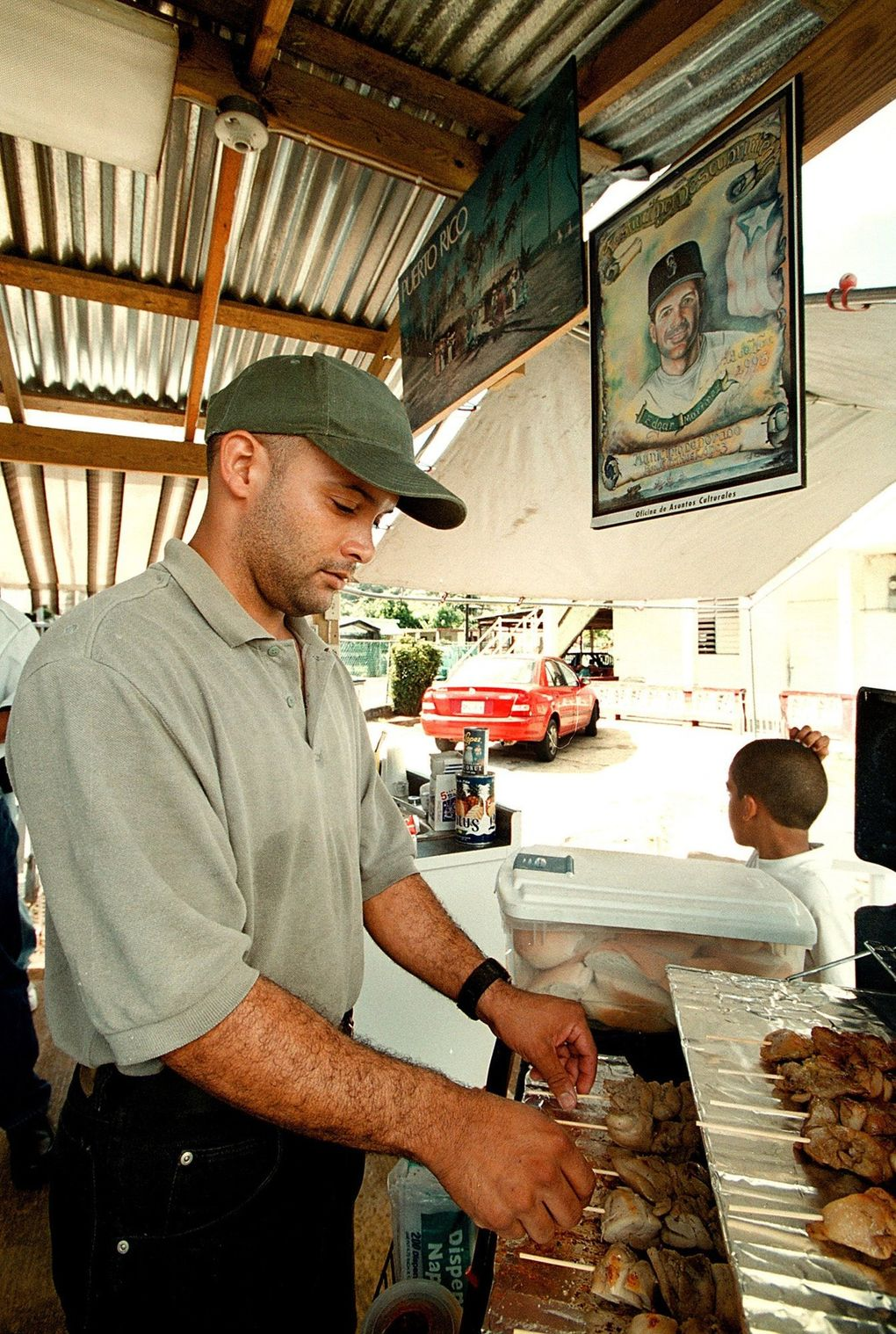 """Jose Santana prepares the traditional Puerto Rican """"Pinchos"""" made of pork and chicken. In the background a painting of Edgar Martinez has a special place in his shop. (Juan Luis Martinez / Special for The Seattle Times)"""