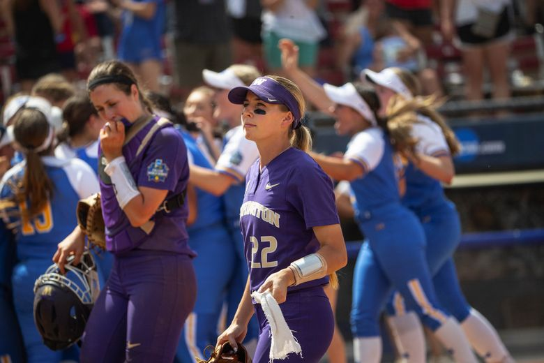 Sis Bates (22) and Morganne Flores walk back to the Washington dugout after a loss to UCLA in the 2019 Women's College World Series.  (Dean Rutz / The Seattle Times)
