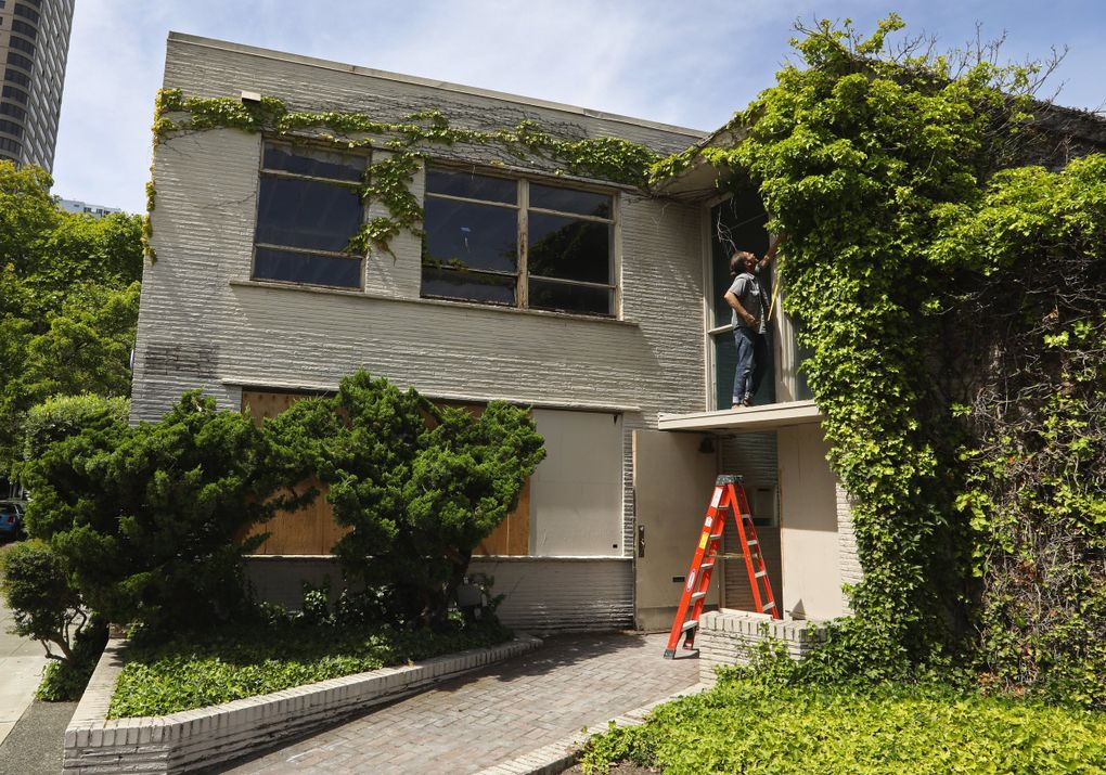 Greg Lundgren takes a tape measure to the windows over the main entrance of this former medical building that he is renovating into Museum of Museums (MoM), which will house two gallery spaces, rotating exhibitions from private collectors and more. (Ken Lambert / The Seattle Times)