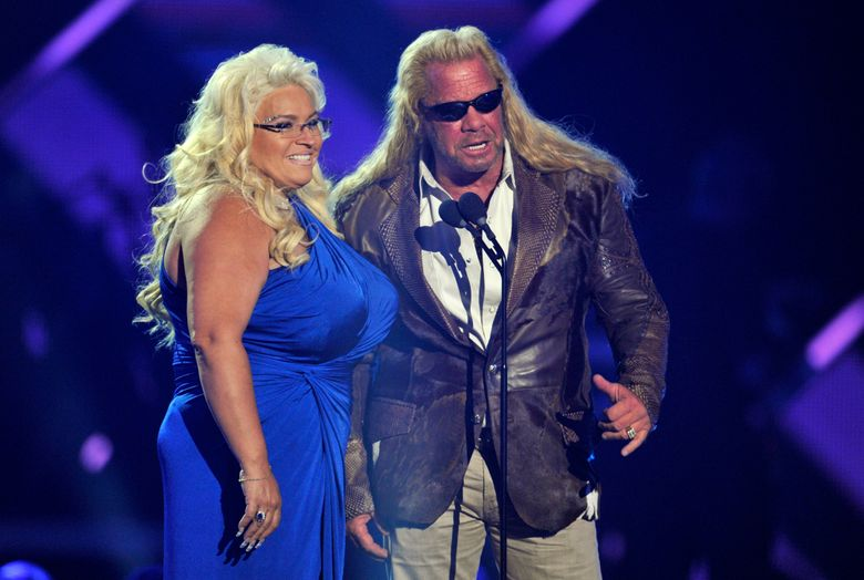 """FILE – In this Wednesday, June 5, 2013, file photo, Duane """"Dog"""" Chapman, right, and Beth Chapman present the award for CMT performance of the year at the CMT Music Awards at Bridgestone Arena in Nashville, Tenn. Beth Chapman is in a medically induced coma in the intensive care unit of Queen's Medical Center in Honolulu, The Honolulu Star-Advertiser reported Sunday, June 23, 2019. Chapman was diagnosed with lung cancer in September 2017 and said in November 2018 that the cancer had returned despite surgery. (Photo by Donn Jones/Invision/AP, File)"""
