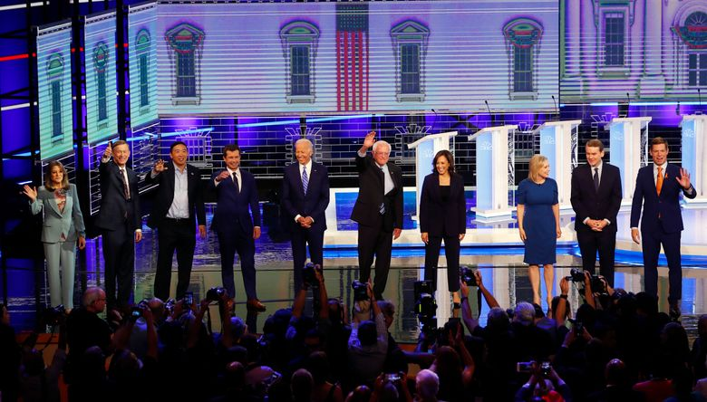 CORRECTS SPELLING OF GILLIBRAND'S FIRST NAME TO KIRSTEN, INSTEAD OF KRISTEN; CORRECTS BENNET'S TITLE TO SEN., INSTEAD OF FORMER SEN. – Democratic presidential candidates from left, author Marianne Williamson, former Colorado Gov. John Hickenlooper, entrepreneur Andrew Yang, South Bend Mayor Pete Buttigieg, former Vice-President Joe Biden, Sen. Bernie Sanders, I-Vt., Sen. Kamala Harris, D-Calif., Sen. Kirsten Gillibrand, D-N.Y., Colorado Sen. Michael Bennet and Rep. Eric Swalwell, D-Calif., wave as they enter the stage for the second night of the Democratic primary debate hosted by NBC News at the Adrienne Arsht Center for the Performing Arts, Thursday, June 27, 2019, in Miami. (AP Photo/Wilfredo Lee)