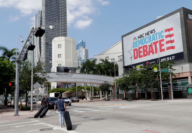 In this June 24, 2019, photo, a billboard advertises the Democratic Presidential Debates across from the Knight Concert Hall at the Adrienne Arsht Center for the Performing Arts of Miami-Dade County, in Miami. Don't envy NBC News executive Rashida Jones, who is behind this week's inaugural Democratic presidential debate and will have to juggle 20 candidates, five news personalities and, it's likely, one tweeting president.. (AP Photo/Lynne Sladky)