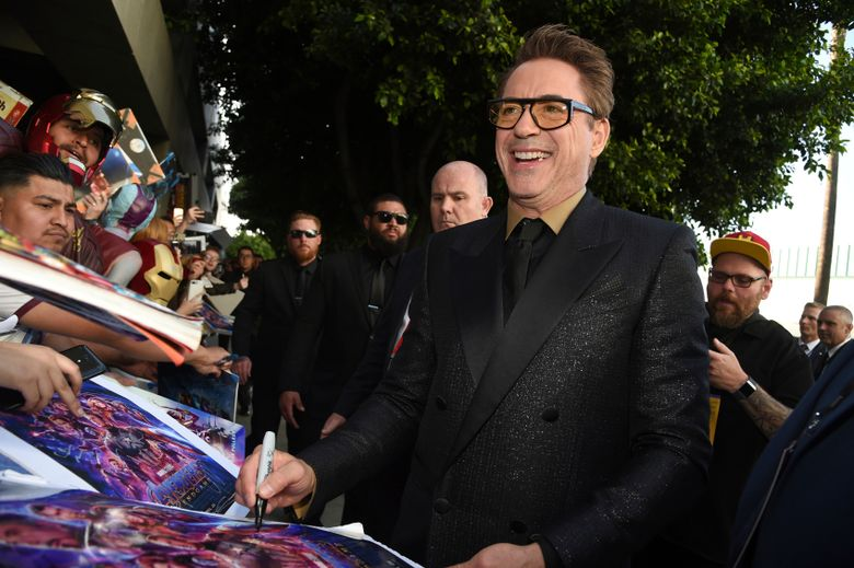 """FILE – In this April 22, 2019, file photo Robert Downey Jr. signs autographs as he arrives at the premiere of """"Avengers: Endgame"""" at the Los Angeles Convention Center. A North Carolina teenager who lost a leg in a shark attack this month got a personal message from the actor who plays """"Iron Man"""" in Marvel's superhero movies. Downey uploaded a video addressed to 17-year-old Paige Winter on his Instagram on Tuesday, June 18, in which he calls her heroic and resilient. (Photo by Chris Pizzello/Invision/AP, File)"""