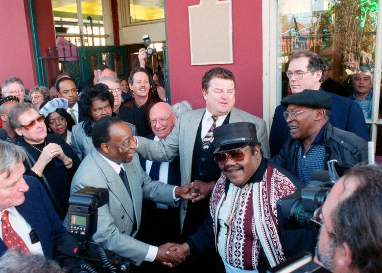 """CORRECTS THAT BARTHOLOMEW IS AT LEFT, NOT RIGHT.  – FILE – In a Dec. 10, 1999 file photo, Fats Domino, center right, shakes hands with Dave Bartholomew, left, amid a crowd of former colleagues at the 50th anniversary observance of Domino's first recording session in New Orleans.  Bartholomew, a giant of New Orleans music and a rock n' roll pioneer who with Fats Domino co-wrote and produced such classics as """"Ain't That a Shame,"""" """"I'm Walkin"""