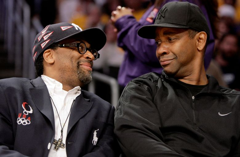 FILE – In this May 19, 2009 file photo, director Spike Lee, left, and Denzel Washington talk during the first half of Game 1 of the NBA basketball Western Conference finals between the Los Angeles Lakers and the Denver Nuggets in Los Angeles. Lee will honor Washington's illustrious career by presenting his friend and collaborator the American Film Institute's Life Achievement Award. AFI says Tuesday, June 4, 2019, that Lee will present the actor and director with the honor at a gala Thursday, June 6 at the Dolby Theatre in Hollywood.  (AP Photo/Mark Avery, File)